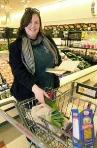 Shopper Marianne Gries picks up a cucumber at Market Basket on Broadway Street in Lowell. SUN/BILL BRIDGEFORD
